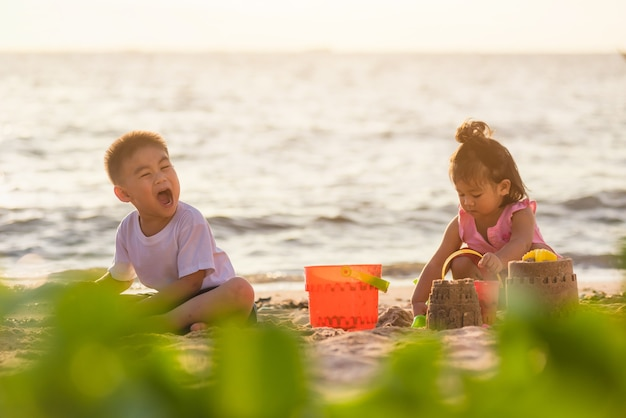 Little boy and girl brother and sister family playing sand with toy sand tools