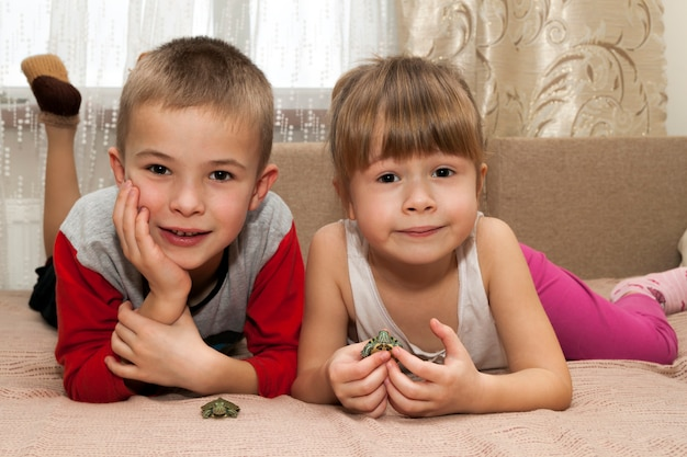 Little boy and girl brother and sister playing together with small turtles animals pets