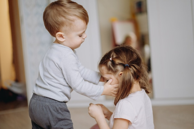 Little boy and a girl brother and sister relations love and care concept