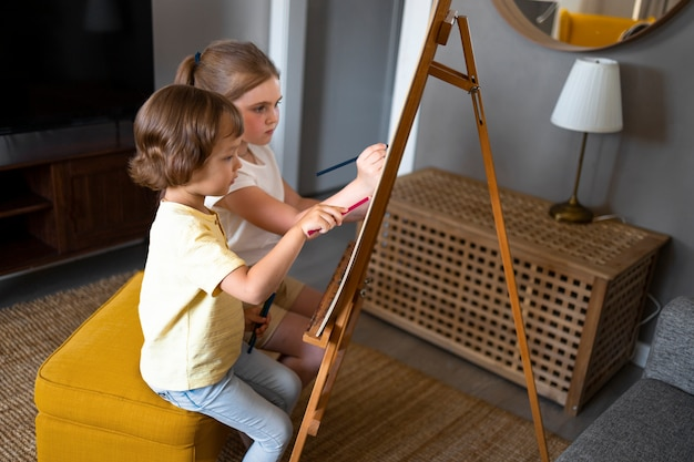 Little boy and girl drawing using easel at home together