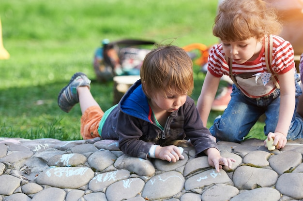 Little boy and girl drawing with sidewalk chalk in the park