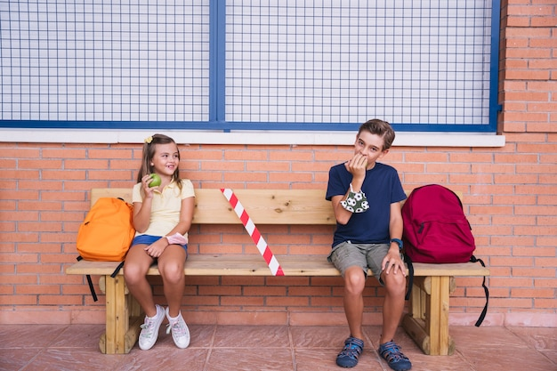 Little boy and girl eating an apple at recess sitting on a bench keeping social distance. back to school during covid pandemic.