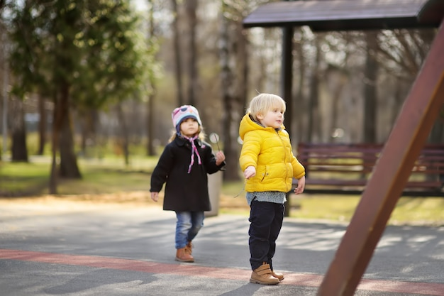 Little boy and girl having fun on outdoor playground on spring or fall day
