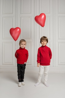 A little boy and girl hold heart-shaped balloons and look at the camera on a white background