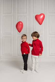 Little boy and girl holding heart balloons on white background