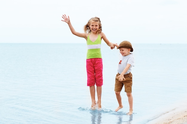 Little boy and girl jumping and having fun in water on the beach seaside
