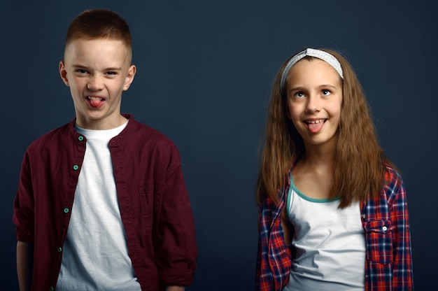 Little boy and girl making faces. happy childhood, children having fun, funny kids isolated on dark background, child emotion