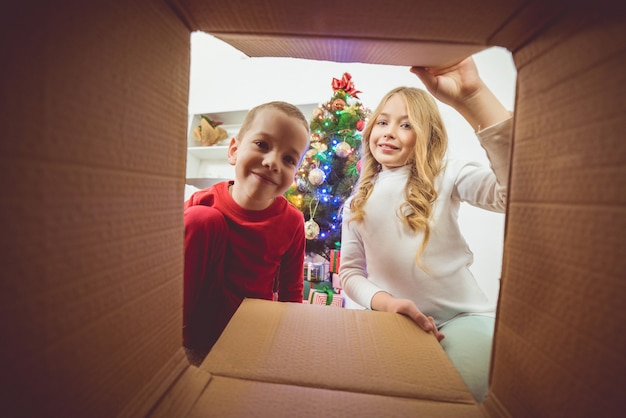 The little boy and a girl open the box on the christmas tree background