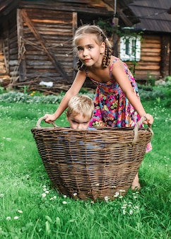 Little boy and girl playing together with hurdled basket in a farm
