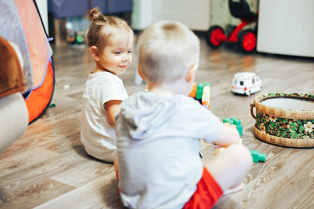 Little boy and girl playing toys at home