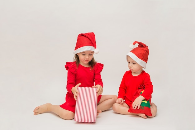 Little boy and girl in red caps open christmas gifts on a white wall with space for text