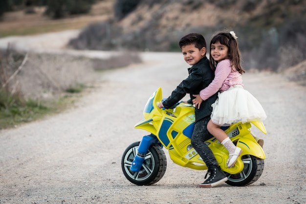 Little boy and girl riding on motorcycle toy