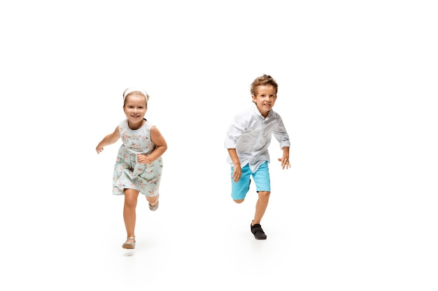 Little boy and girl running on white background