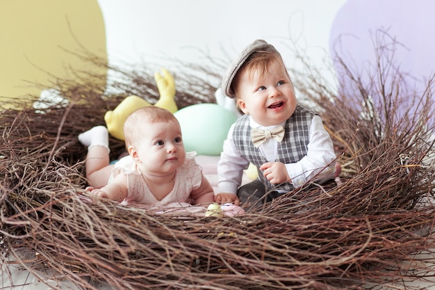 Little boy and girl sitting in natural nest with colorful easter eggs.