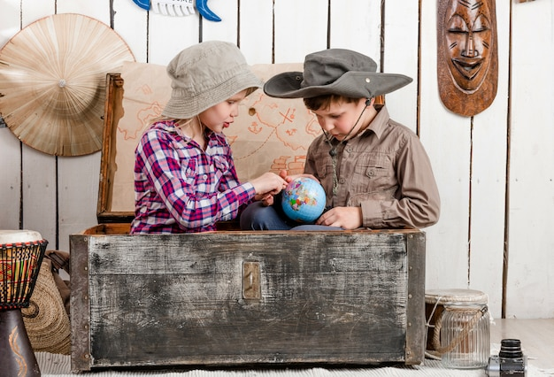 Little boy and girl study globe in big chest