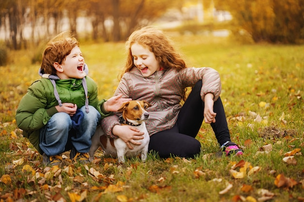Little boy and girl with her puppy jack russell in autumn outdoors.