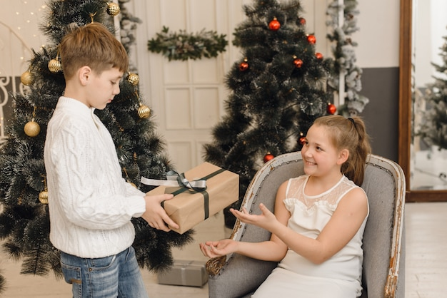 Little boy gives a cute girl a christmas present in a bright interior