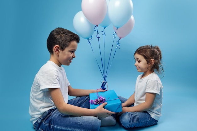 A little boy gives a gift to a little girl sitting in front of him against a surface of pink and blue balloons on a blue surface
