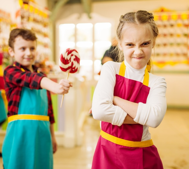 男の子は頑固な女の子に手作りのロリポップを与えます。ペストリーショップでのワークショップの子供たち。キャンディストアでの休日の楽しみ。焼きたての砂糖キャラメル