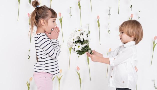 Маленький мальчик дарит цветы девушке