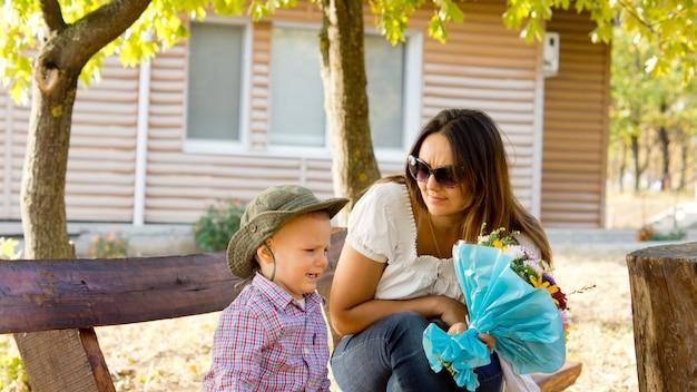 キャビン近くの素朴なベンチでママに彼女への愛を示すために花束を与える小さな男の子