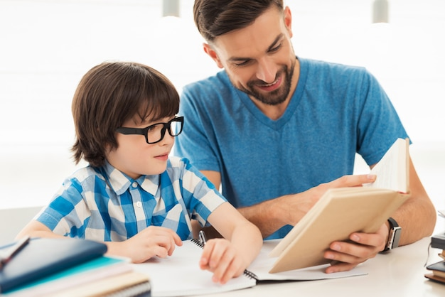 Little boy in glasses doing homework with father.