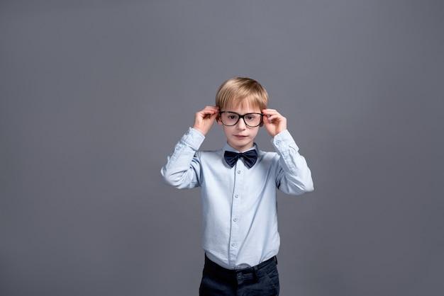 Little boy in glasses posing on grey