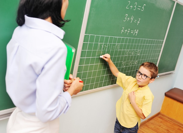 A little boy in glasses writes with chalk on the blackboard and looks at the teacher in the backgrou...
