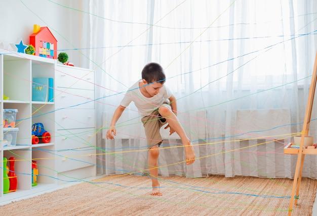 ロープの網を通過する小さな男の子