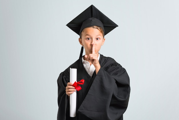 Little boy graduating showing a sign of closing mouth and silence gesture on grey background