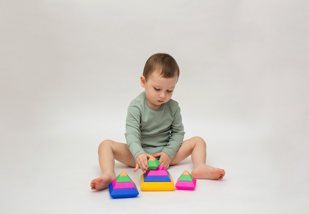 Little boy in a green bodysuit sits and collects a pyramid on a white background