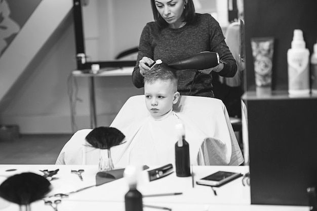 Little boy at the hairdresser. child is scared of haircuts. hairdresser's hands making hairstyle to little boy, close up. fashionable haircut for boys.