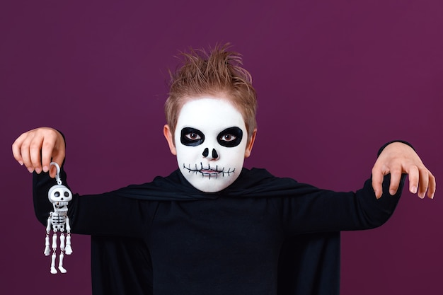 Little boy in halloween costume holds skeleton and scares the camera on purple background. halloween makeup.