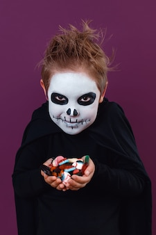 Little boy in halloween costume holds sweets looking at the camera on purple background. halloween makeup.