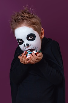 Little boy in halloween costume holds sweets and treat it on purple background. halloween makeup.