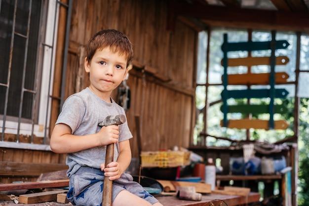 어린 소년은 목수의 작업장에서 나무 판자에 망치로 못을 망치로 친다