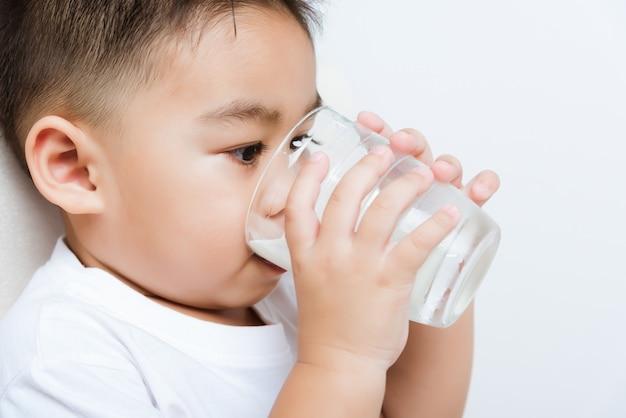 어린 소년 손을 잡고 그 동안 흰 우유를 마시는 우유 유리