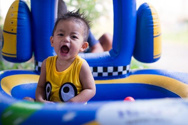 Маленький мальчик счастлив с детским бассейном
