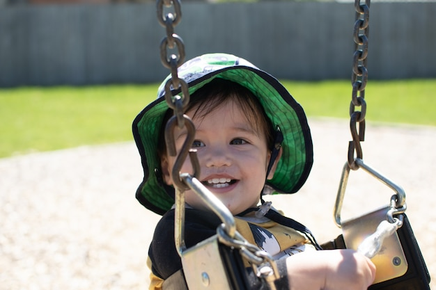 Little boy has very beautiful smile when playing swing in a sunshine day