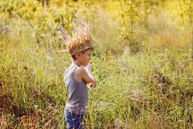 Little boy have a crown from dry grass on the head and swords in hands. joy and play concept