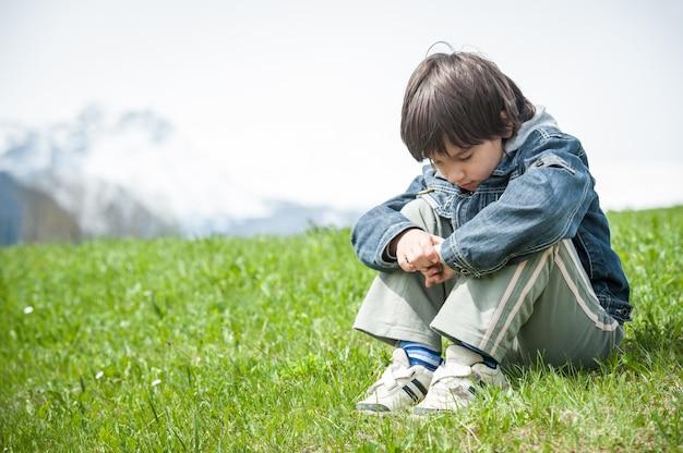 牧歌的なアルプスの美しい春の休暇を持つ小さな男の子