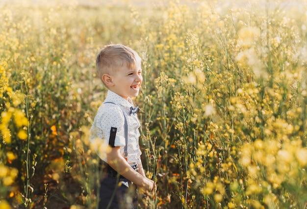 어린 소년은 여름에 자연 속에서 카메라를 향해 손을 흔들며 즐겁게 놀고 있습니다. 유지종자 강간 밭에 있는 귀여운 사랑스러운 아이, 클로즈업 초상화