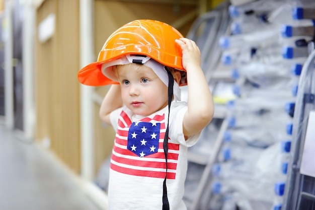 Little boy having fun in a hardware store. toddler builder choosing the right helmet in a hardware store.