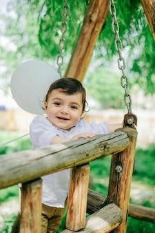Маленький мальчик веселится в красочном саду и стоит на скамейке-качелях