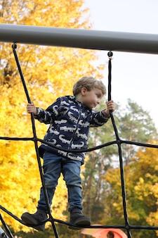 Маленький мальчик веселится на игровой площадке в красивом парке с сухими желтыми и красными листьями. осенняя семейная прогулка в лесу.
