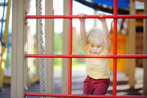 Little boy having fun on outdoor playground. summer active sport leisure for kids