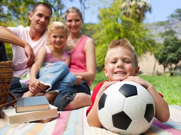 彼の家族とサッカーボールで楽しい小さな男の子