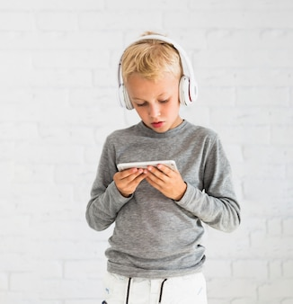 Little boy having fun with smartphone and earphones