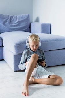 Little boy having fun with tablet and earphones