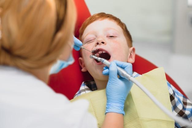 Little boy having his teeth examined by a dentist